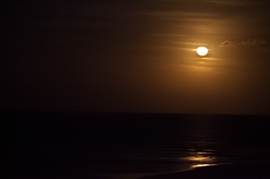 Moon rise over the bay with golden waves.